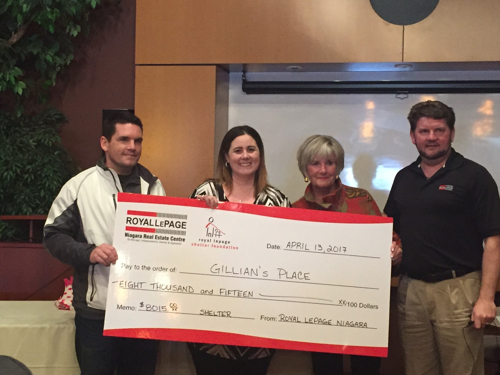 Royal LePage employees present cheque to Gillian's Place Manager.